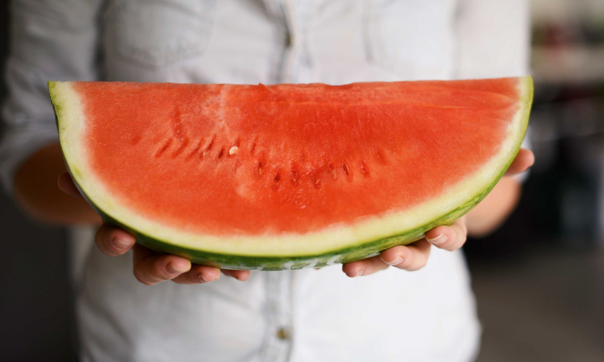 A person holding a big wedge of seedless watermelon