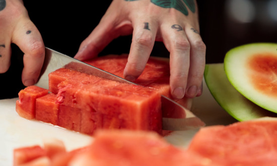 watermelon cubes being cut. hand and knife shown in process of cutting, cut rind on side