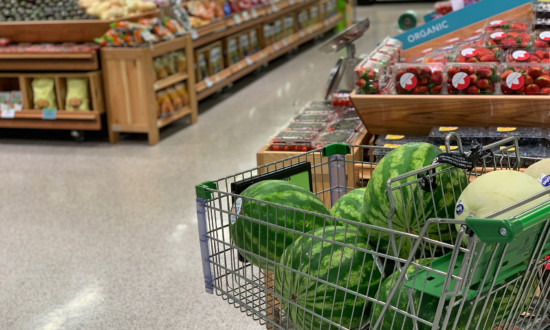 five whole watermelon in shopping cart in produce department of grocery store