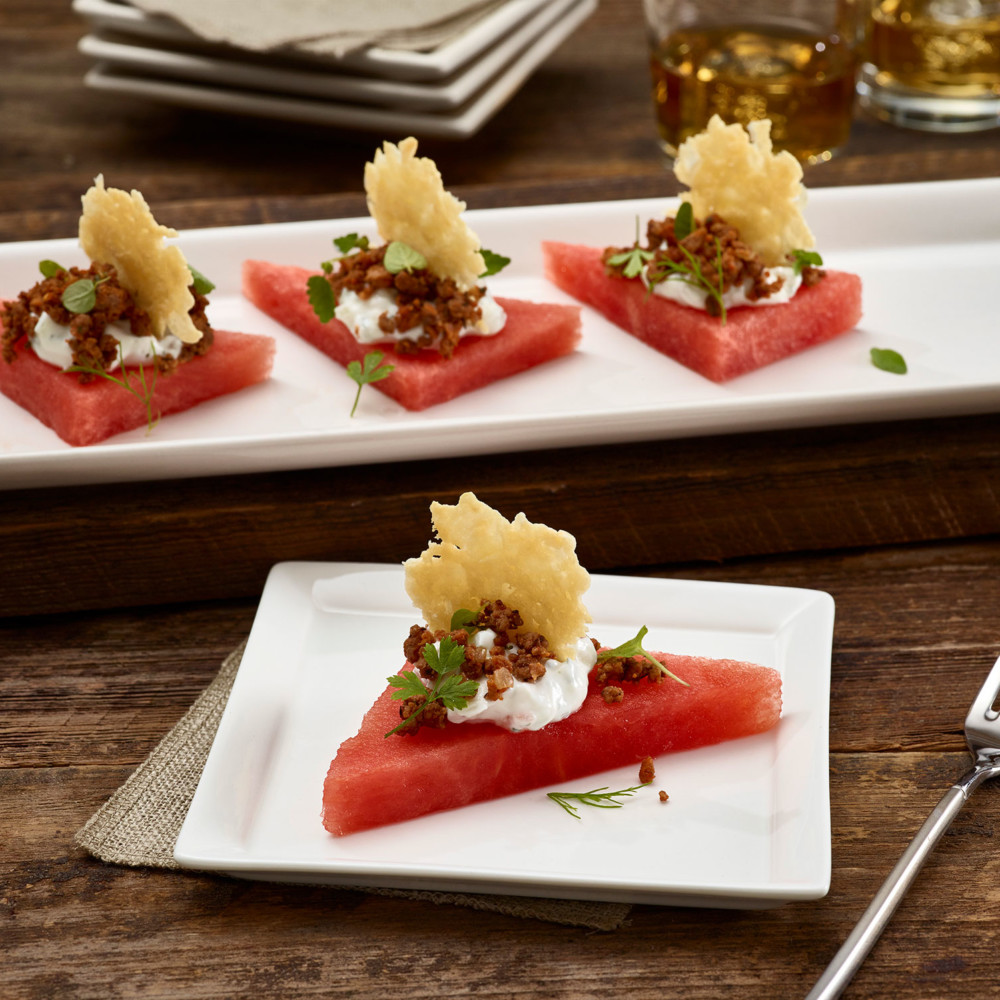 Watermelon Lamb Chorizo Bites on a rectangular serving plate with one served on appetizer plate.