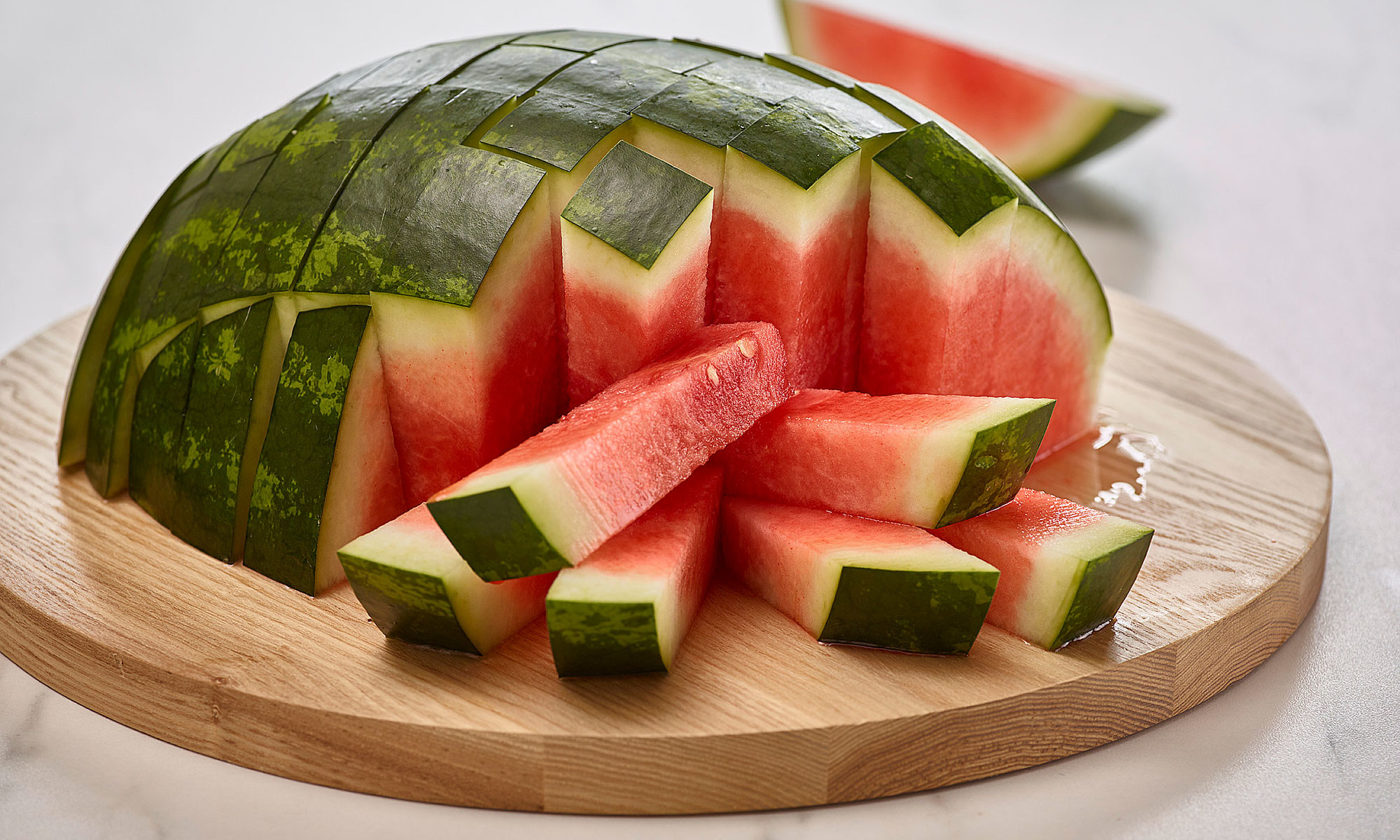 half watermelon cut into sticks on top of round wooden cutting board