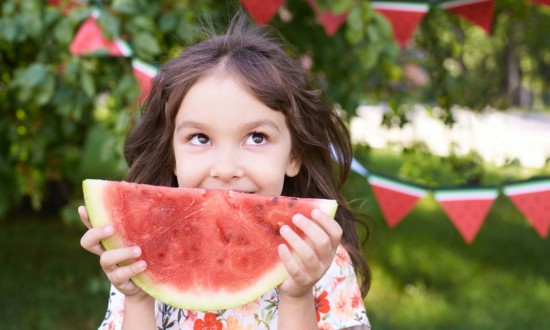 young girl holding watermelon slice with watermelon streamers in background, outdoors