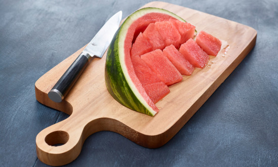 watermelon wedge with flesh cut away from rind on wooden cutting board with knife on side