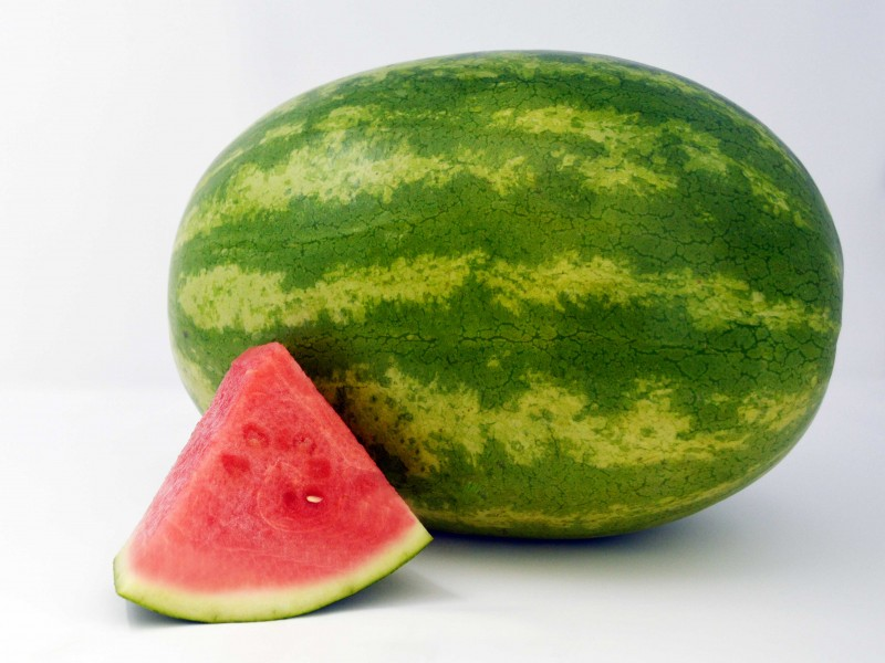 whole watermelon with triangular cut of watermelon in foreground