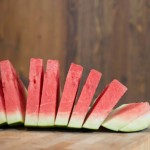 Accordion slices (triangular cuts) of red watermelon on wooden cutting board