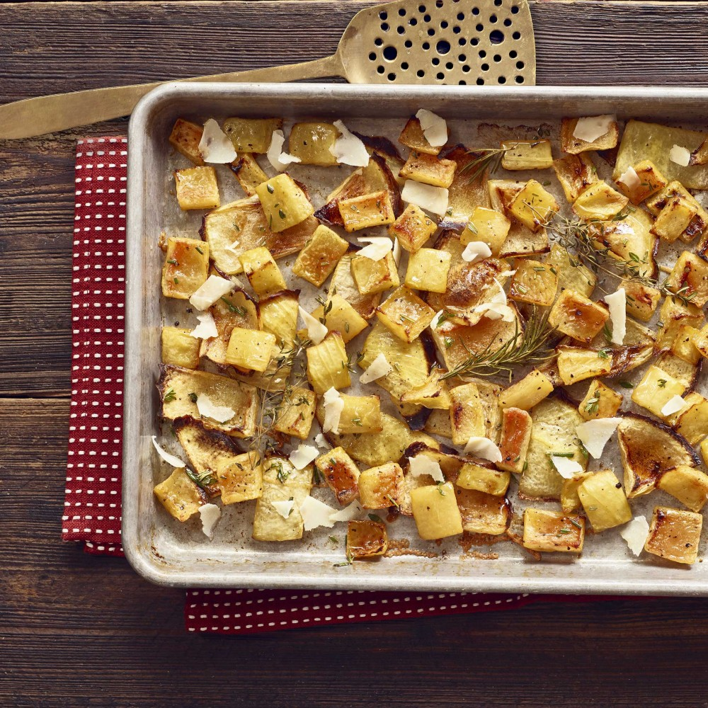 Roasted Rind Parmesan in baking pan with spatula on side. Set on red with white polkadot napkin on wooden table