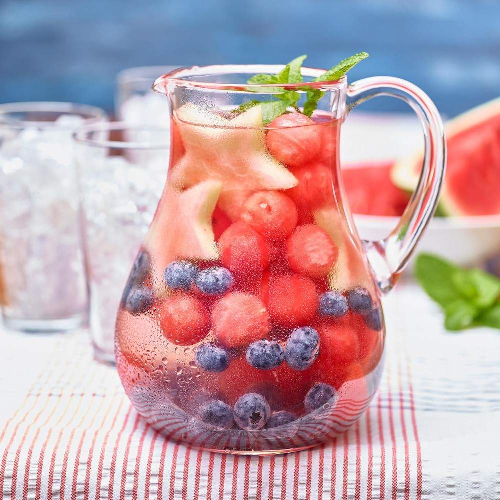 Watermelon Infused Water in pitcher filled with fruit (watermelon balls, blueberries, mint garnish. Clear glasses filled with crushed ice in background, also watermelon wedge in background. Set on red and white thin striped tablecloth