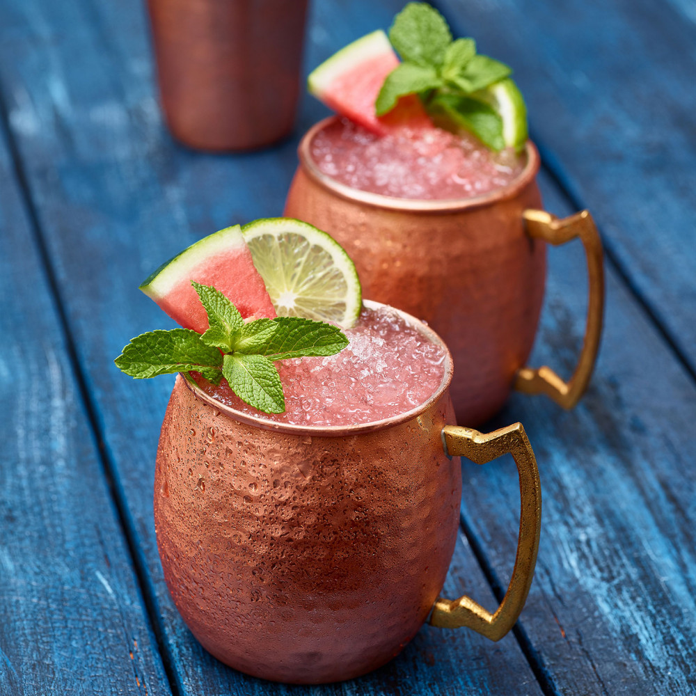Watermelon Mule (x2) in copper cups garnished with watermelon slice, lime and mint. Copper shaker in background. Set on blue painted table