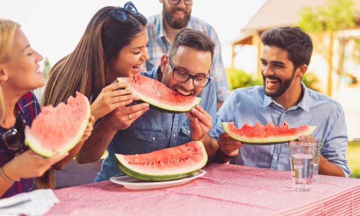 group of friends, three men, two women at outdoor picnic table wit red and white gingham tablecloth, eating watermelon wedges