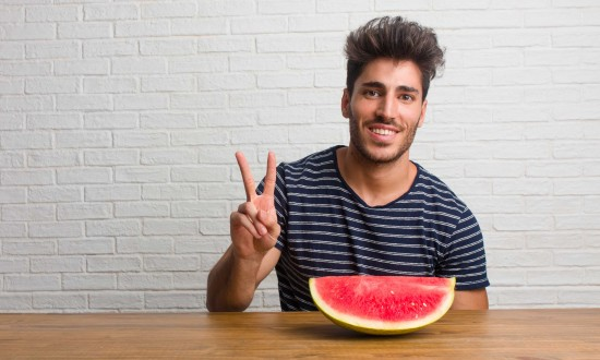 man at table with wedge of watermelon in front of him. He's making peace sign