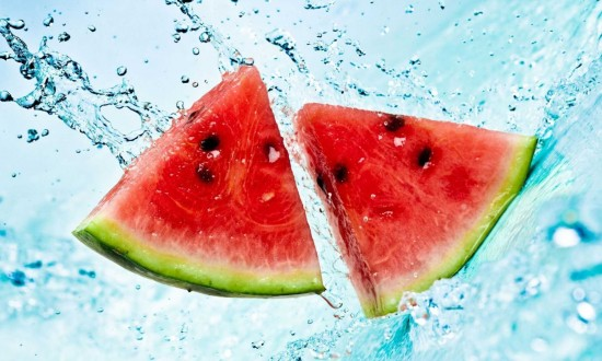 two watermelon triangular cuts being splashed with water,