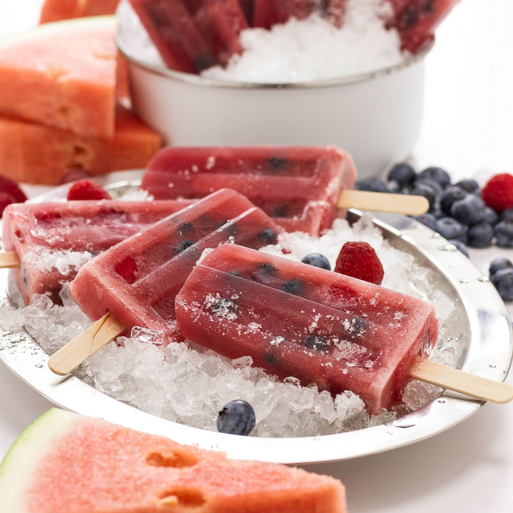 Berry Popsicles set in metal bowls with crushed ice. Garnished with blueberries, raspberries and triangular watermelon cuts on side.