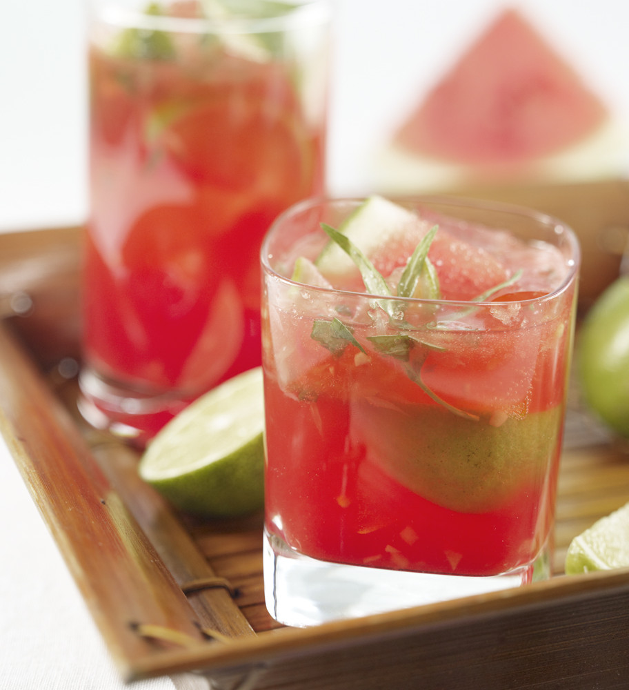 Two Watermelon Caipirinhas served in bamboo serving tray garnished with tarragon leaves and lime. Watermelon wedge in background.