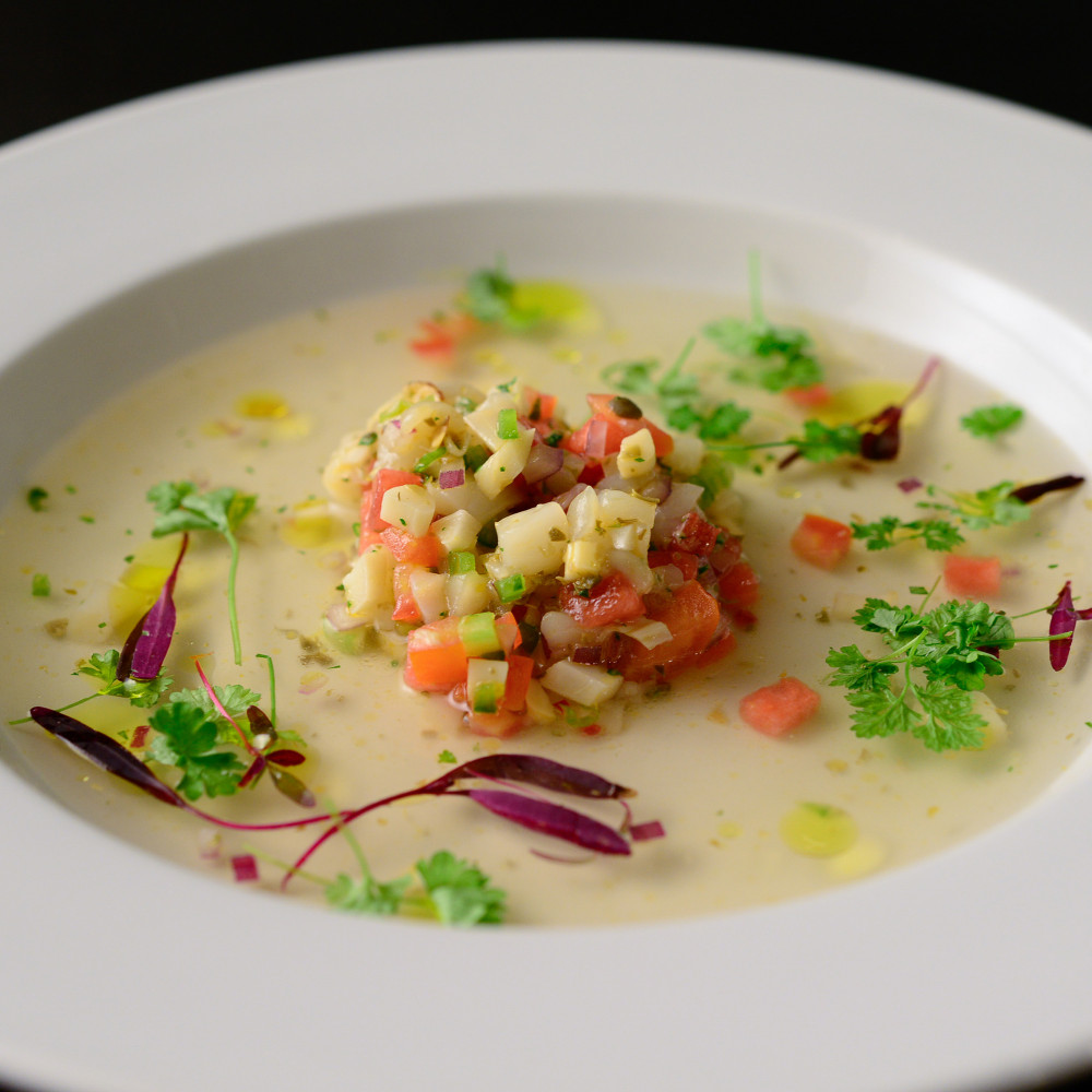 Watermelon Consomme with Scallop Ceviche in wide rimmed bowl.