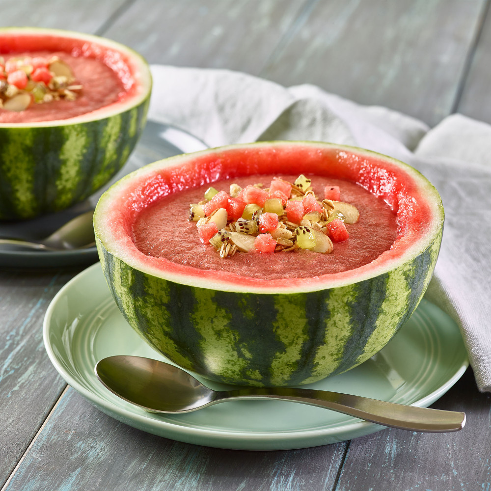 Two Watermelon Crunch Smoothie Bowls served in mini watermelon ½ round of rind. Garnished with watermelon, kiwi and slivered almonds.