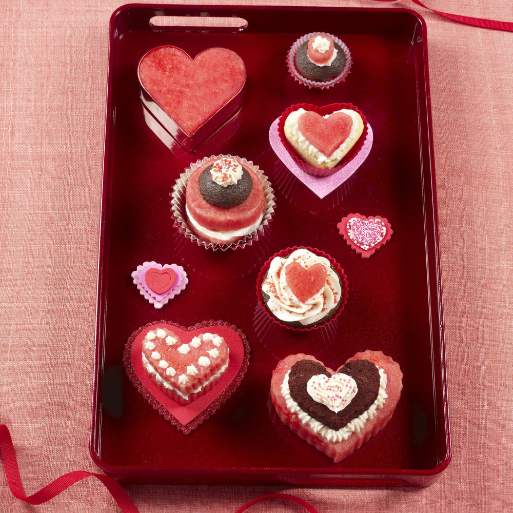 Watermelon cutouts, heart shaped & round, some with brownie set on red serving tray. Light red tablecloth with red ribbon above and below tray