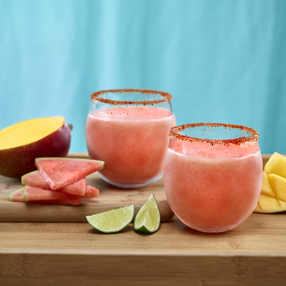Watermelon Mango Margaritas in Tajin spice rimmed glasses. Garnishes of watermelon, mango and lime.