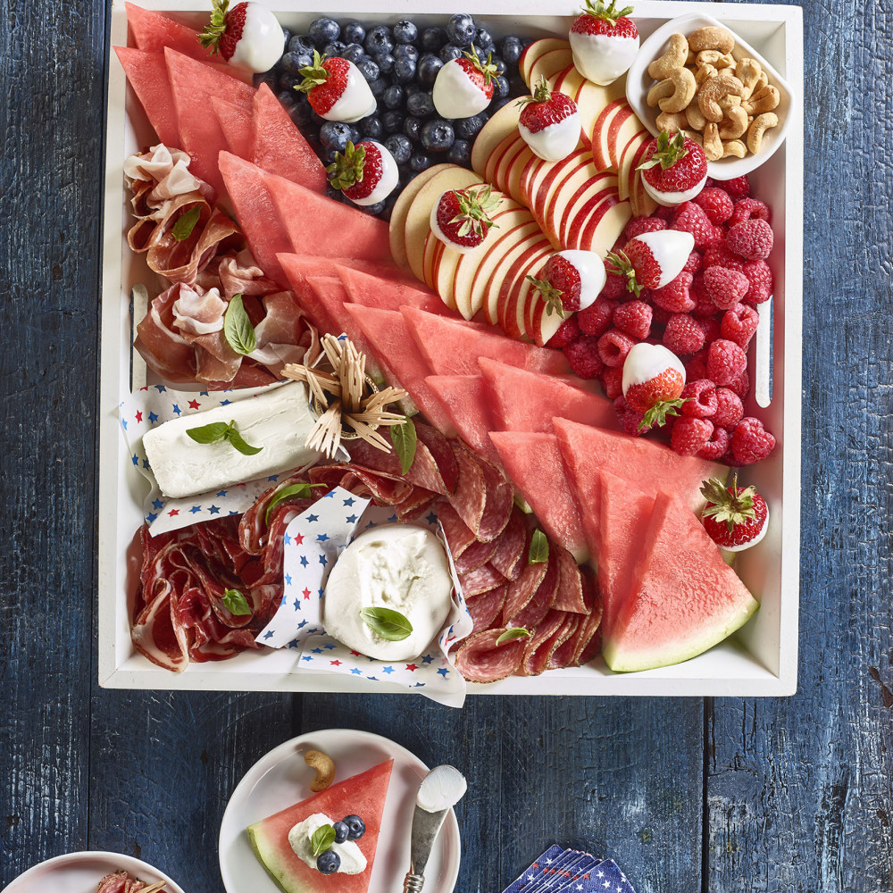 Patriotic Board Charcuterie set in square serving tray (triangular cut watermelon slices, raspberries, strawberries, blueberries, nuts, cheese, deli meats set on blue painted table