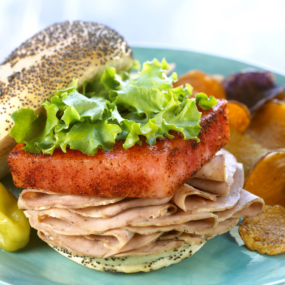 watermelon pork sandwich on turquoise plate, poppyseed bun with greens and pepper as side garnish with multi-colored potato chips