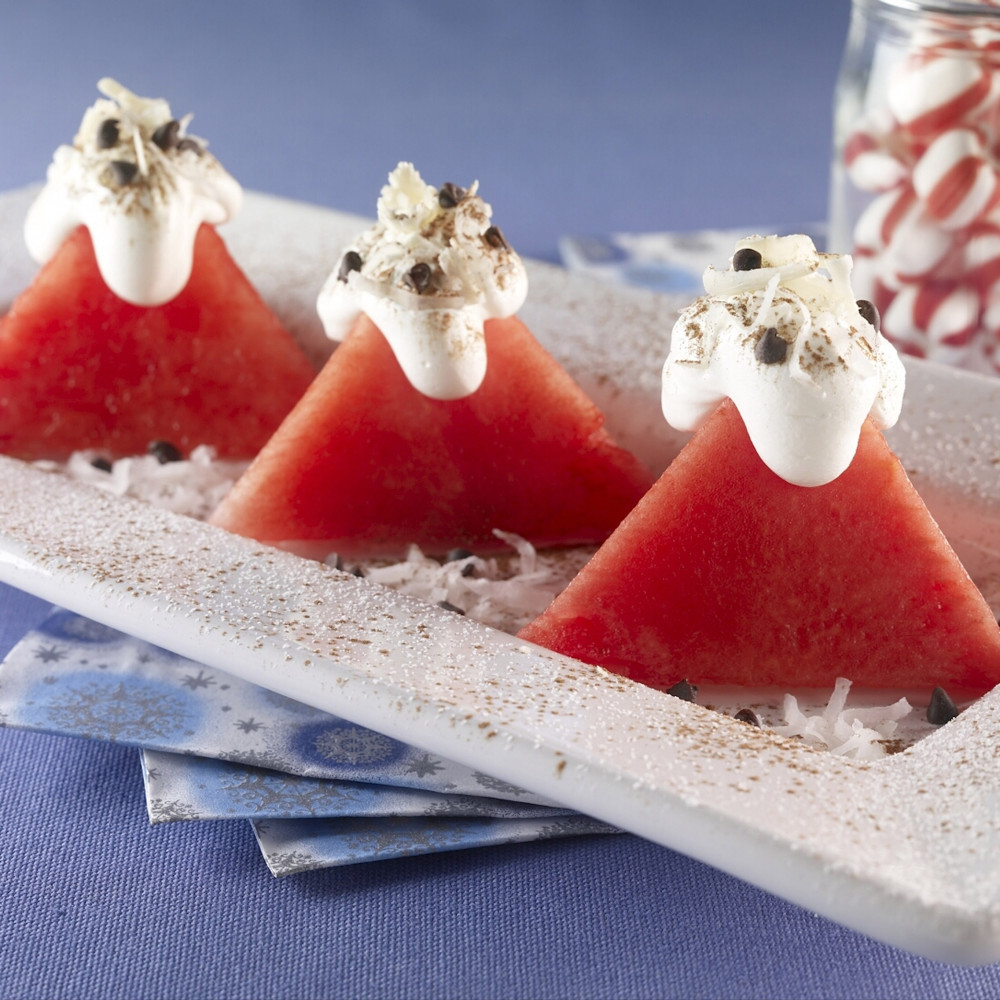 Three pyramid shaped watermelon cuts served on rectangular plate topped with whipped cream, shredded coconut, white chocolate shavings and mini chocolate chips. Jar of peppermint candies in background.