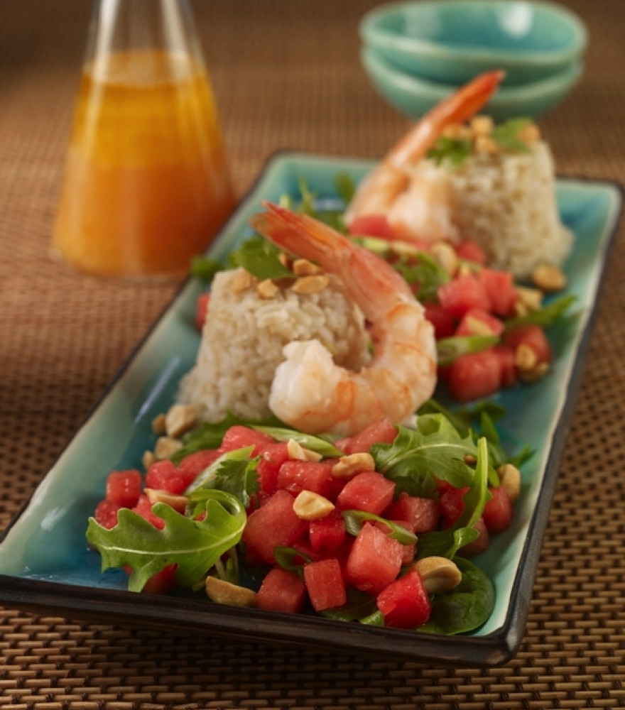 Thai Watermelon Salad served on rectangular teal colored plate, topped with shrimp. Cruet of dressing in background.