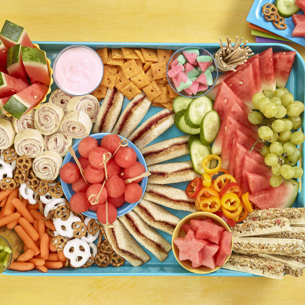 Kids grazing board overhead shot showing sandwiches, cracker, watermelon and other fruit