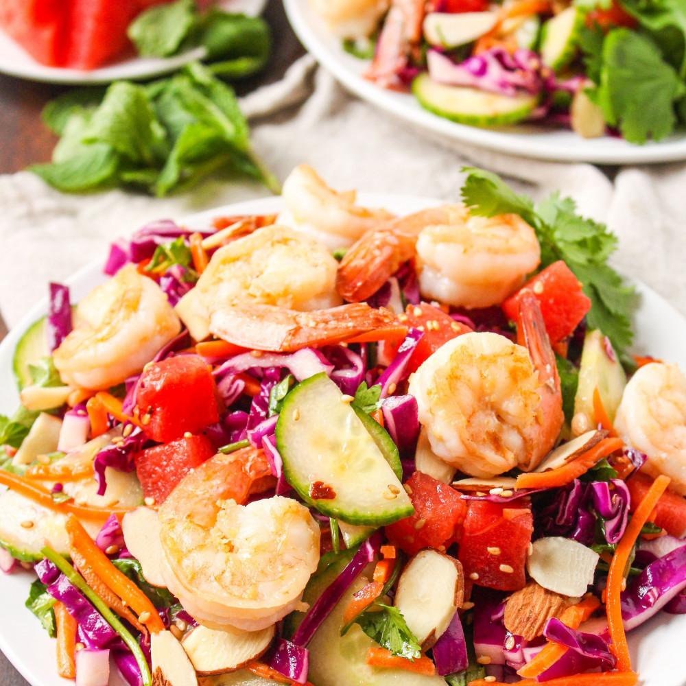 sesame shrimp and watermelon salad on plate with 2nd plate in background. Also in background, watermelon wedges